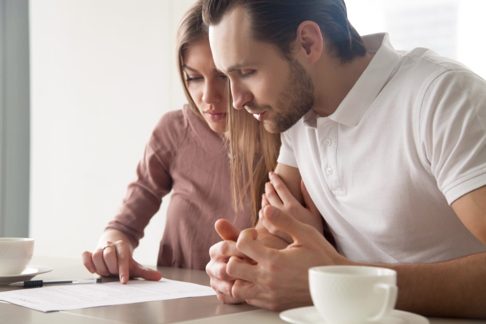 A male and female couple sitting in front of a laptop sorting out their life insurance policy