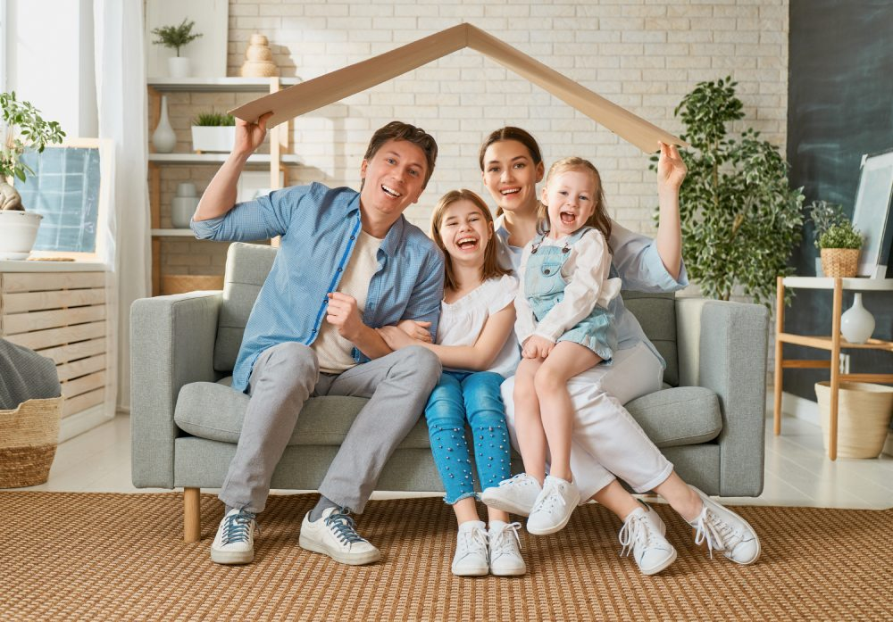 A happy family of four sitting on a couch with a novelty wooden roof being held up inciting they are covered with mortgage insurance