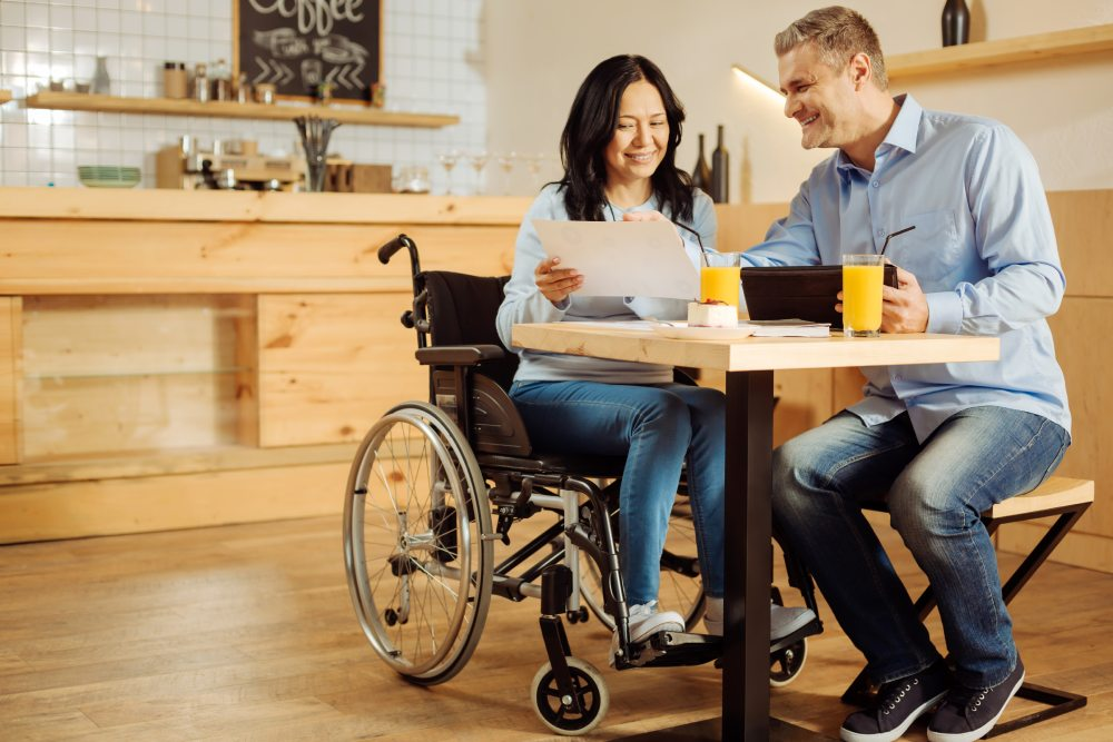 A woman in a wheelchair sitting with a man at a desk happily discussing her disability income protection policy