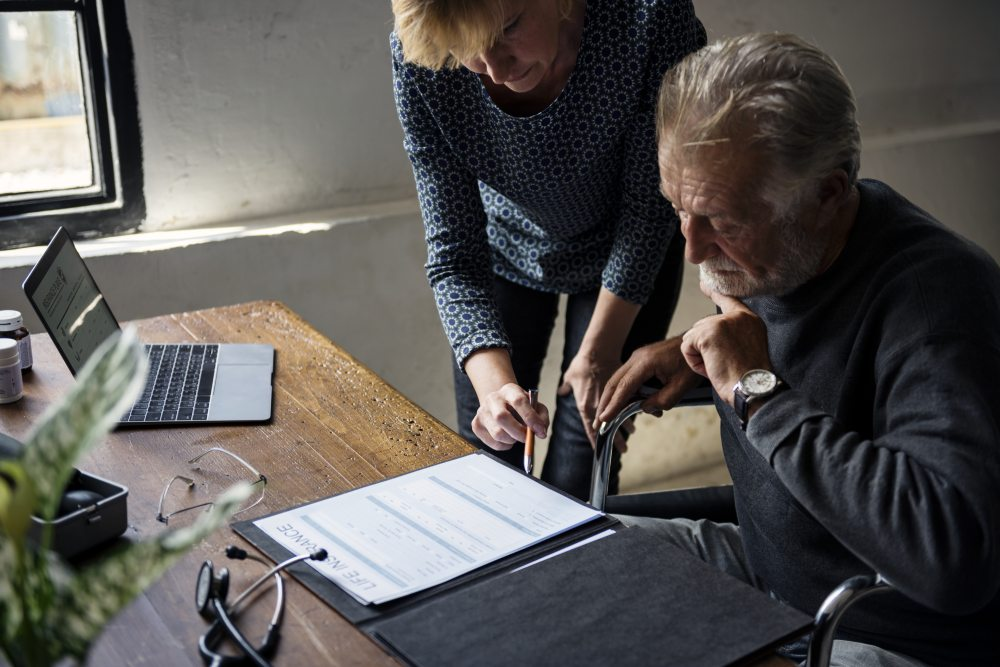 A senior citizen being informed by a younger woman about his trauma insurance policy in front of a laptop